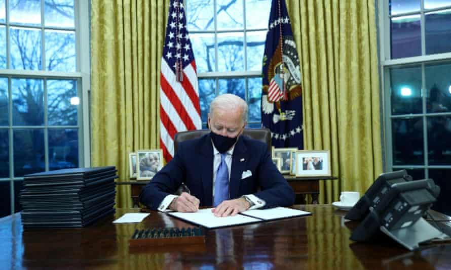 Joe Biden ký các mệnh lệnh điều hành trong Phòng Bầu dục sau khi nhậm chức. Ảnh: Tom Brenner / Reuters